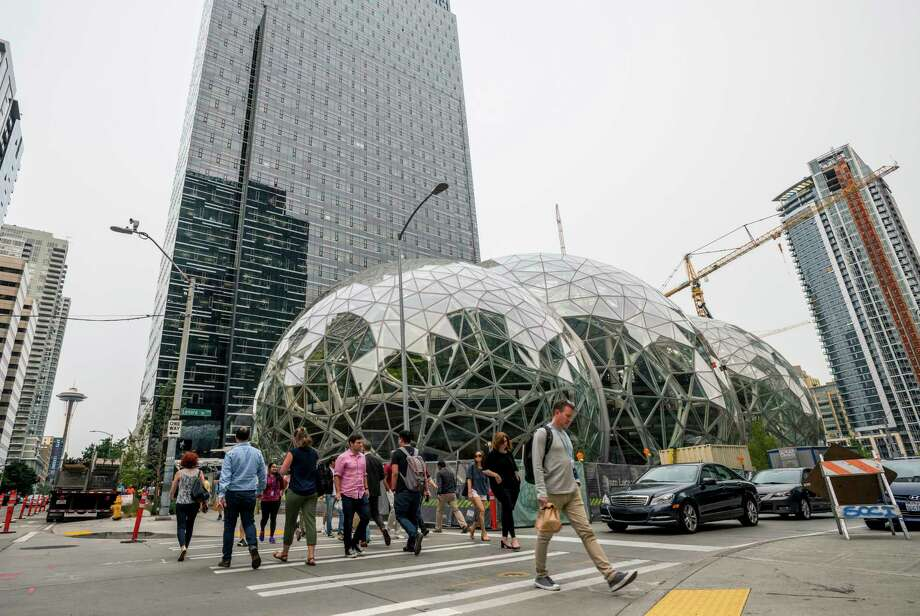 Pedestrians walk past a recently built trio of geodesic domes that are part of the Seattle headquarters for Amazon, Sept. 7, 2017. The online retail giant said it was searching for a second headquarters in North America in 2017, a huge new development that would cost as much as $5 billion to build and run, and house as many as 50,000 employees. (Stuart Isett/The New York Times) Photo: STUART ISETT, STR / NYTNS