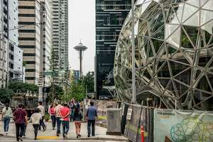 With the Space Needle observation tower visible in the distance, pedestrians walk past a recently built trio of geodesic domes that are part of the Seattle headquarters for Amazon, Sept. 7, 2017. The online retail giant said it was searching for a second headquarters in North America in 2017, a huge new development that would cost as much as $5 billion to build and run, and house as many as 50,000 employees. (Stuart Isett/The New York Times)