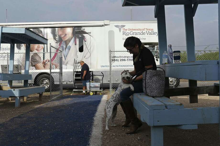 Research Assistant Stephanie Leal, 25, plays with an neighborhood dog as the University of Texas Rio Grande Valley School of Medicine Unimovil is set up in the Indian Hills colonia of Mercedes, Texas, Wednesday, Sept. 27, 2017. The program was founded in 2014 to create a substantial health care model for underserved communities. In 2016, Unimovil was added. It has two examination rooms, a laboratory, a restroom and diagnostic equipment. Photo: JERRY LARA / San Antonio Express-News / San Antonio Express-News