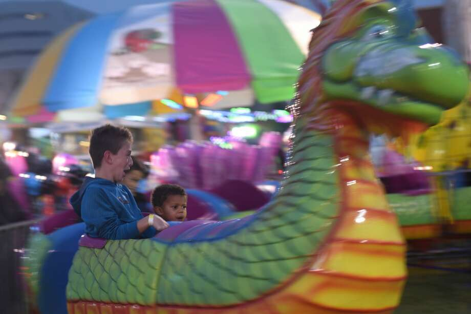 From left, Colton and Blake Meek ride the Dragon Wagon at the St. Ann's Family Fair and carnival Sept. 28, 2017, at St. Ann's.  James Durbin/Reporter-Telegram Photo: James Durbin