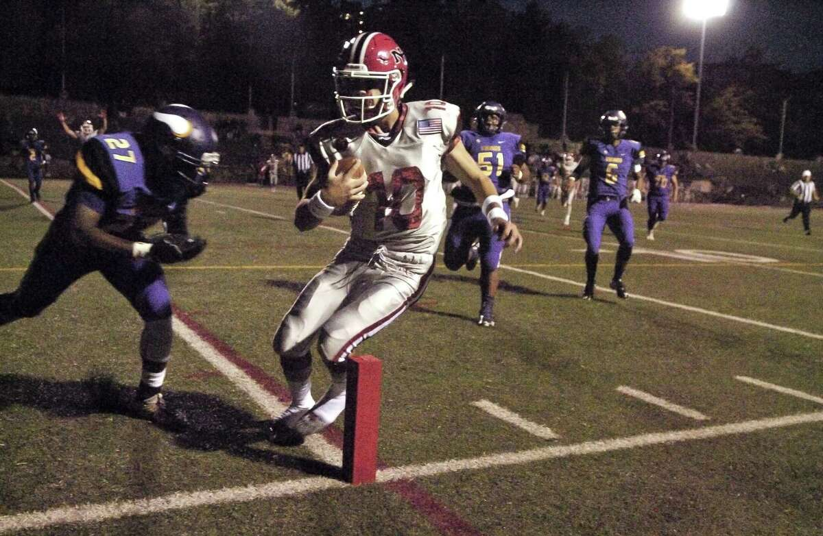 New Canaan quarterback Drew Pyne runs in for a touchdown in the first quarter against Westhill Alan Nowlin in a FCIAC football game at Boyle Stadium in Stamford, Connecticut on Thursday, Sept. 28, 2017.