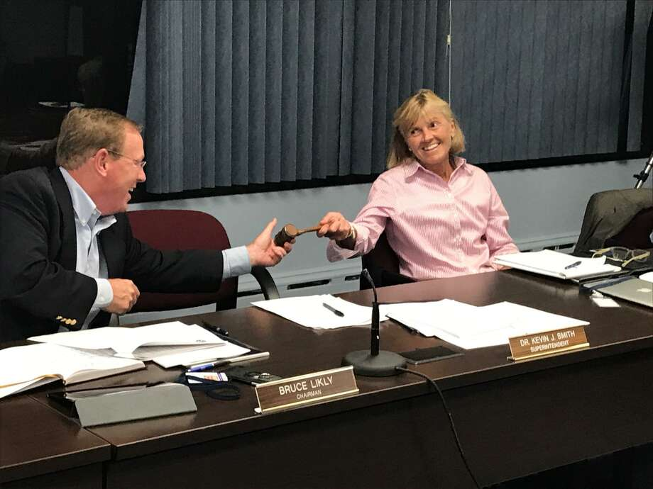 Bruce Likly passes the gavel to Christine Finkelstein, after announcing his resignation as the Wilton Board of Education chairman on Thursday, Sept. 28, 2017. Photo: Contributed Photo