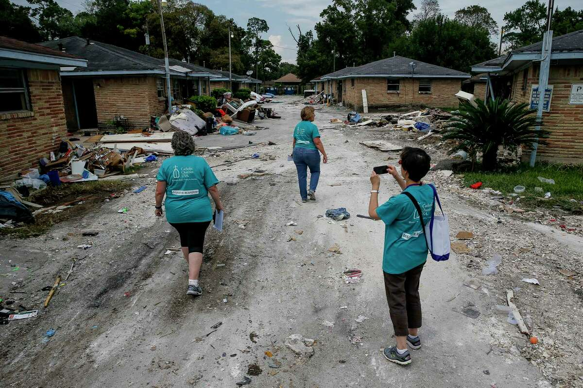 Catholic Charities USA members, from left, Helene Lauffer, from New York City, Becky VanPool, from Oklahoma City, and Molly O'Donnell, from Portland, Ore., walk through a group of apartments that flooded as they canvas the Kashmere Gardens area.