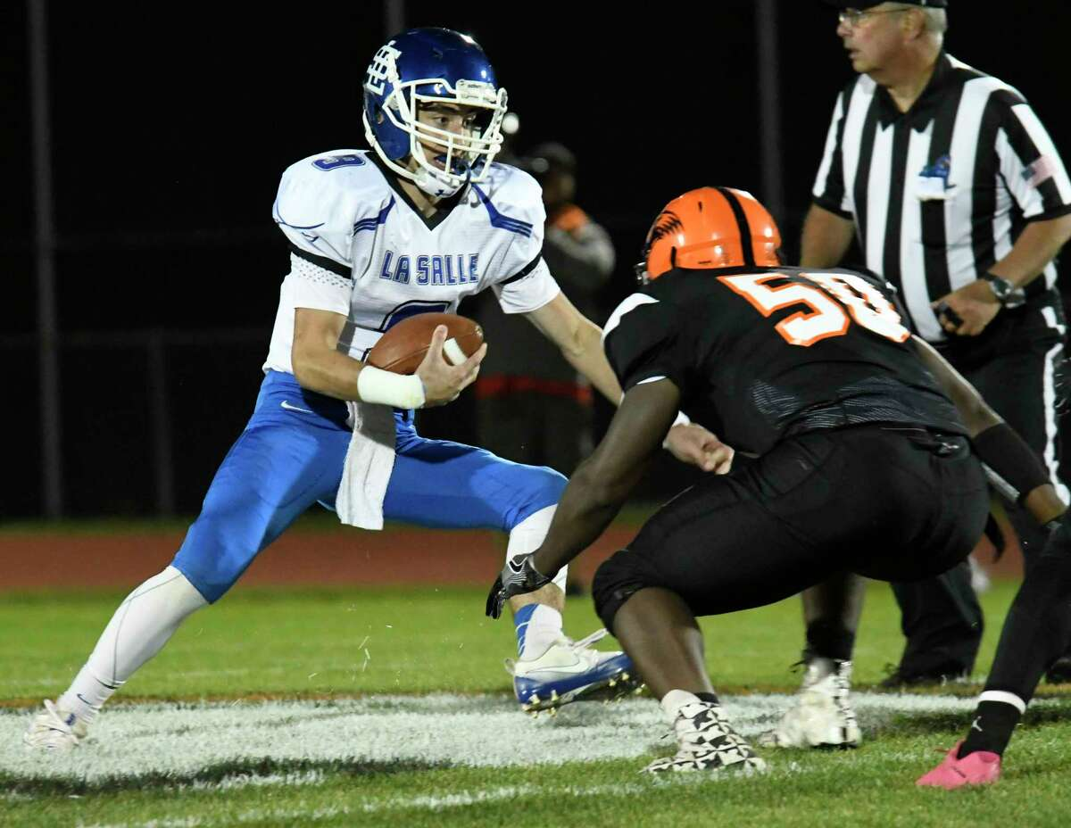 La Salle quarterback Dermott McDonough faces Bethlehem line back Kendell Harris as he runs for a first down during a game on Thursday in Bethlehem. (Jenn March/Special to the Times Union)