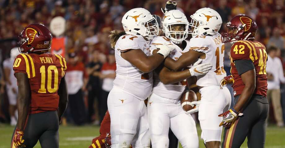 Texas running back Chris Warren III, center, celebrates with teammates after he scored a touchdown against Iowa State during the first half of an NCAA college football game, Thursday, Sept. 28, 2017, in Ames, Iowa. (AP Photo/Charlie Neibergall) Photo: Charlie Neibergall/Associated Press
