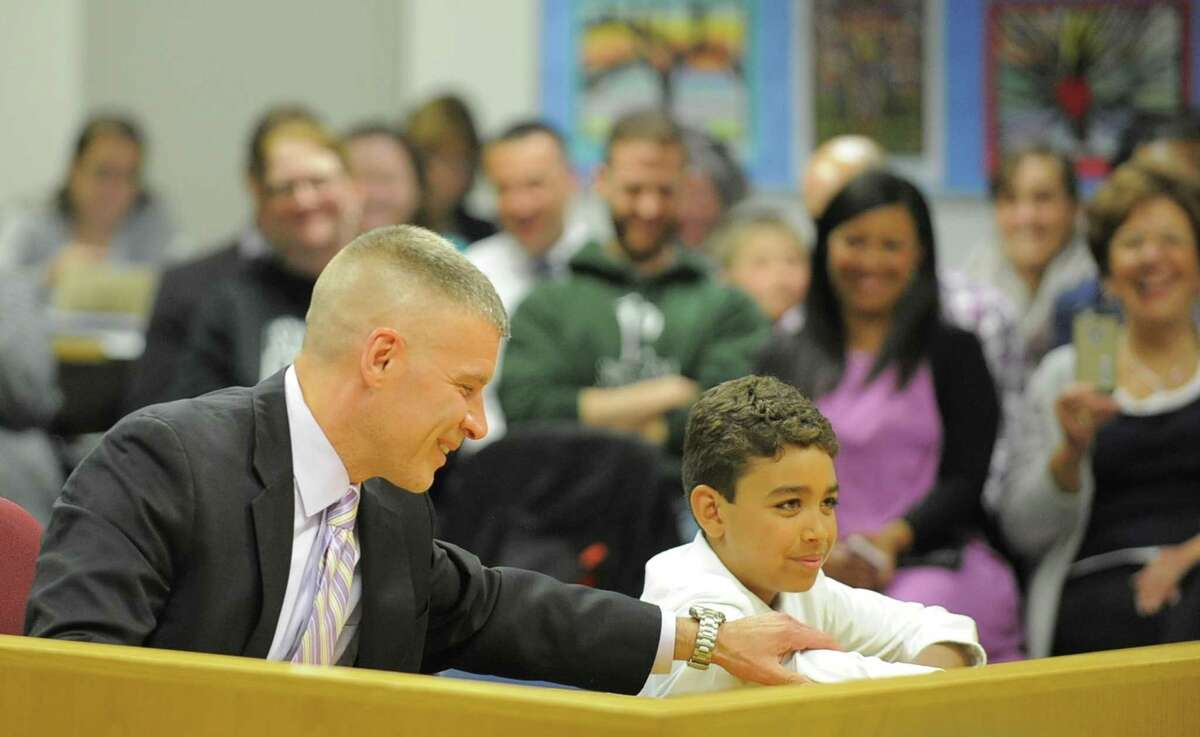 Michael Rinaldi, at left, smiles with his son Nikolas after being appointed Westhill High School principal by the Stamford Board of Education in April.