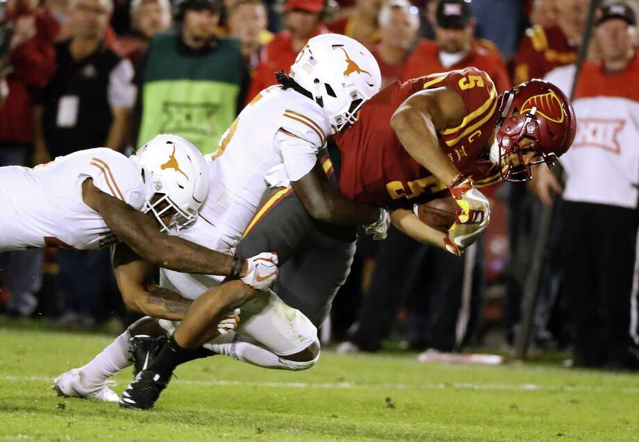 AMES, IA - SEPTEMBER 28: Wide receiver Allen Lazard #5 of the Iowa State Cyclones is tackled by defensive back DeShon Elliott #4, and defensive back Holton Hill #5 of the Texas Longhorns, as he rushed for yards in the second half of play at Jack Trice Stadium on September 28, 2017 in Ames, Iowa.  The Texas Longhorns won 17-7 over the Iowa State Cyclones. (Photo by David Purdy/Getty Images) Photo: David Purdy, Stringer / Getty Images / 2017 Getty Images