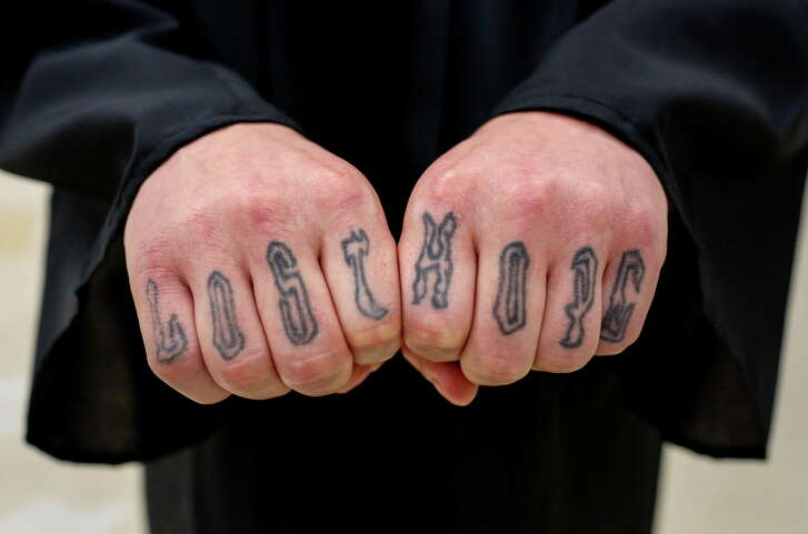 """Brandon Brewer shows off tattoos on his fingers that read, """"Lost Hope,"""" during a graduation ceremony for Darrington Unit inmates who earned degrees from the Southwestern Baptist Theological Seminary, Monday, May 8, 2017, in Rosharon. Brewer is serving a 60-year sentence for murdering his mother. """"Even though I lost hope, God brought me to a place where hope does not exist, so I can be a beacon of hope for others,"""" he said."""