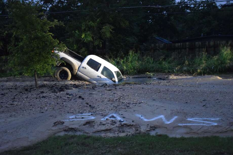 An off-duty police officer crashed his pickup truck into a sinkhole Friday morning on the Southeast Side. Photo: Caleb Downs / San Antonio Express-News