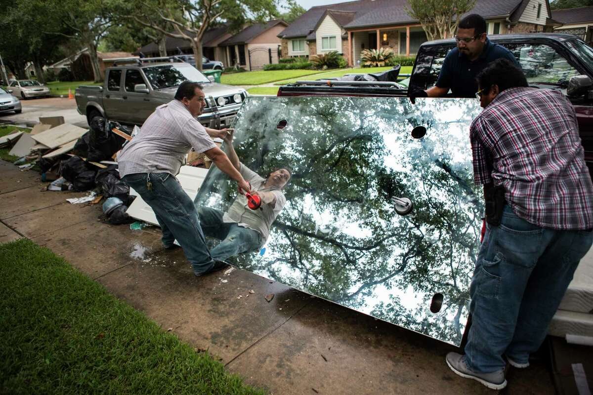 Edwin Cerritos, left, Louis Cerritos and Oscar Cerritos place a large mirror onto the debris pile outside a Meyerland area home, that was flooded in the aftermath of Hurricane Harvey, as they continue restoration work on Thursday, Sept. 21, 2017, in Houston. The house had been newly renovated and is now being gutted by Legal Eagle Contractors. ( Brett Coomer / Houston Chronicle )