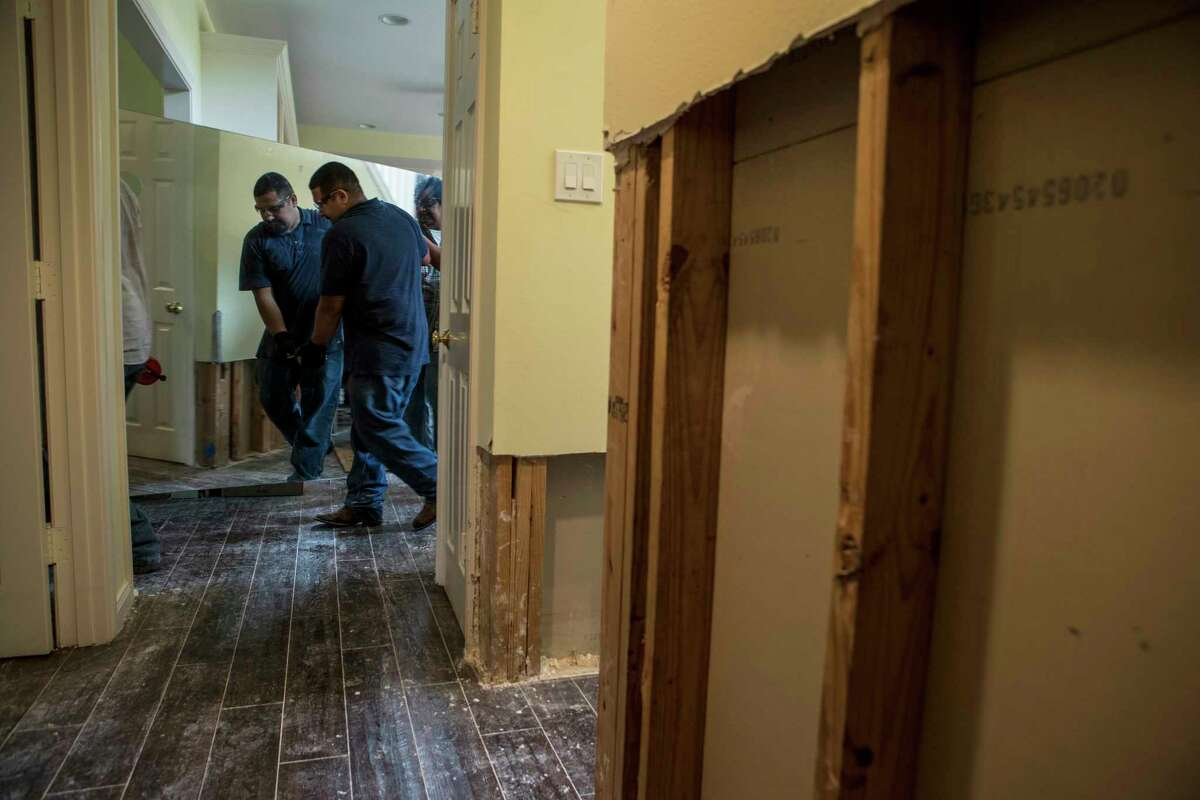 Louis Cerritos helps carry a mirror from a Meyerland area home, that was flooded in the aftermath of Hurricane Harvey, as they continue restoration work on Thursday, Sept. 21, 2017, in Houston. The house had been newly renovated and is now being gutted by Legal Eagle Contractors. ( Brett Coomer / Houston Chronicle )