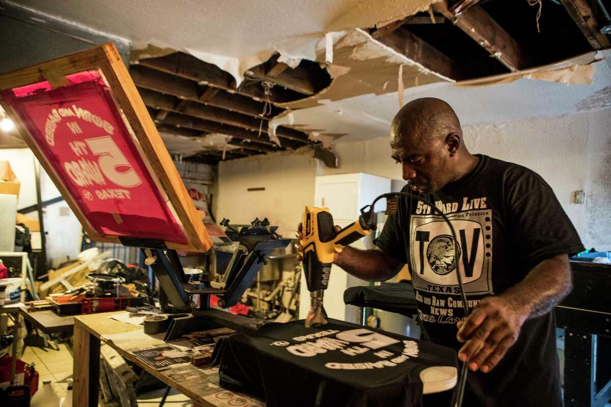 Art Smith dries the ink on a t-shirt he just printed at Super Bold Print Shop on Tuesday, Sept. 19, 2017, in Houston. The storefront T-shirt print shop's roof and walls were damaged in the floods in the aftermath of Hurricane Harvey. Their T-shirt drying machine left waterlogged and inoperable, heavily damaging their home and business. ( Brett Coomer / Houston Chronicle )
