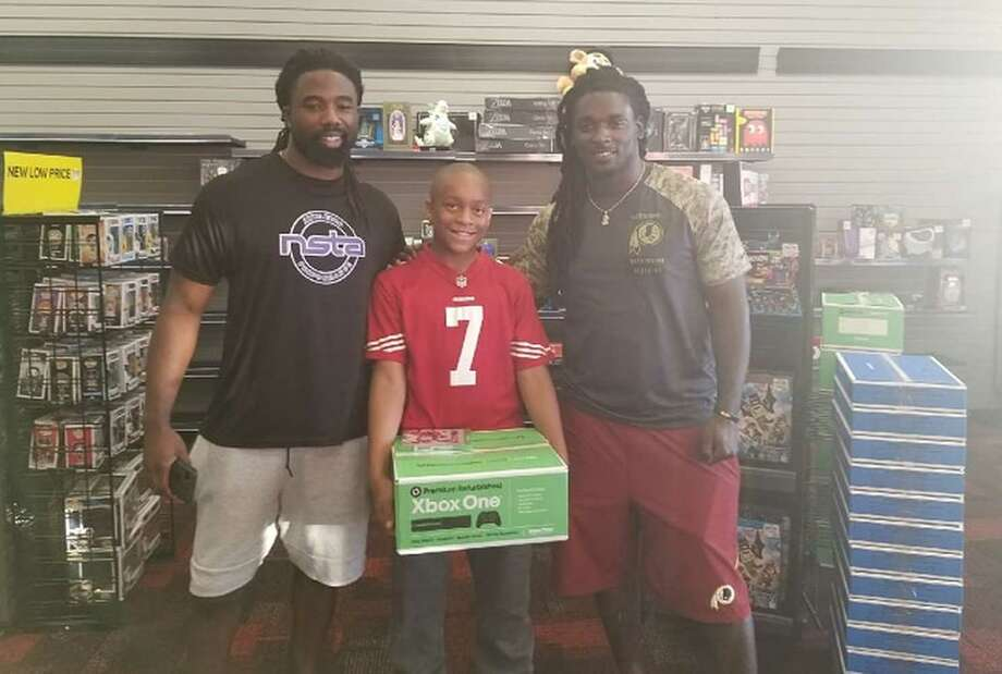 Washington Redskins running backs Keith Marshall and Rob Kelley pose with 10-year-old Jaden Watts, middle, after buying him an Xbox at a Virginia GameStop. Photo: Saundra Watts