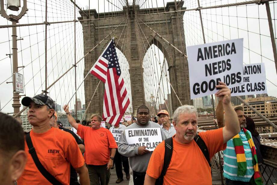 Following a rally in Brooklyn, N.Y., at Cadman Plaza Park on Sept. 18, hundreds of union members march across the Brooklyn Bridge in support of IBEW Local 3 (International Brotherhood of Electrical Workers). Photo: Drew Angerer / Getty Images / 2017 Getty Images