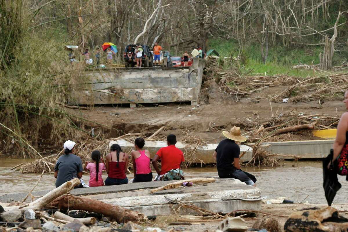 People sit on both sides of a destroyed bridge that crossed over the San Lorenzo de Morovis river, in the aftermath of Hurricane Maria, in Morovis, Puerto Rico, Wednesday, Sept. 27, 2017. A week since the passing of Maria many are still waiting for help from anyone from the federal or Puerto Rican government. But the scope of the devastation is so broad, and the relief effort so concentrated in San Juan, that many people from outside the capital say they have received little to no help. (AP Photo/Gerald Herbert) ORG XMIT: PRGH115