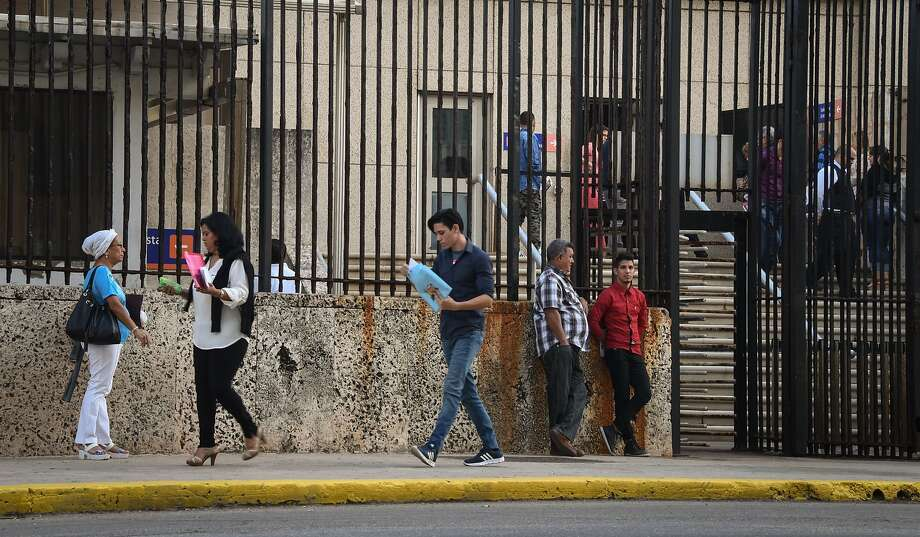 People walk near the U.S. Embassy in Havana last year. More than half the staff is being withdrawn. Photo: ADALBERTO ROQUE, AFP/Getty Images