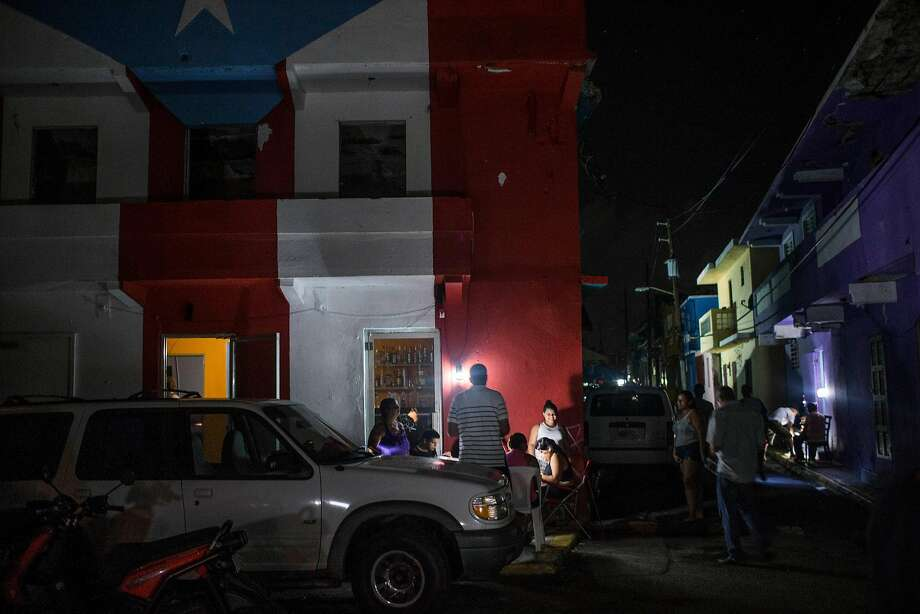 With power still out following Hurricane Maria, residents of the La Perla neighborhood of San Juan, Puerto Rico, use portable lights distributed by the city government. Photo: DENNIS M. RIVERA PICHARDO, For The Washington Post