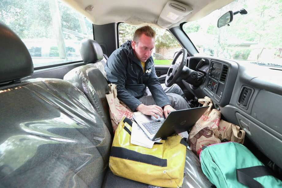 Houston Chronicle Reporter St. John Barned-Smith works from the inside of a pick-up truck while covering the aftermath of Hurricane Harvey in the Columbia Lakes subdivision Wednesday, Aug. 30, 2017, in West Columbia. Photo: Steve Gonzales, Houston Chronicle / © 2017 Houston Chronicle