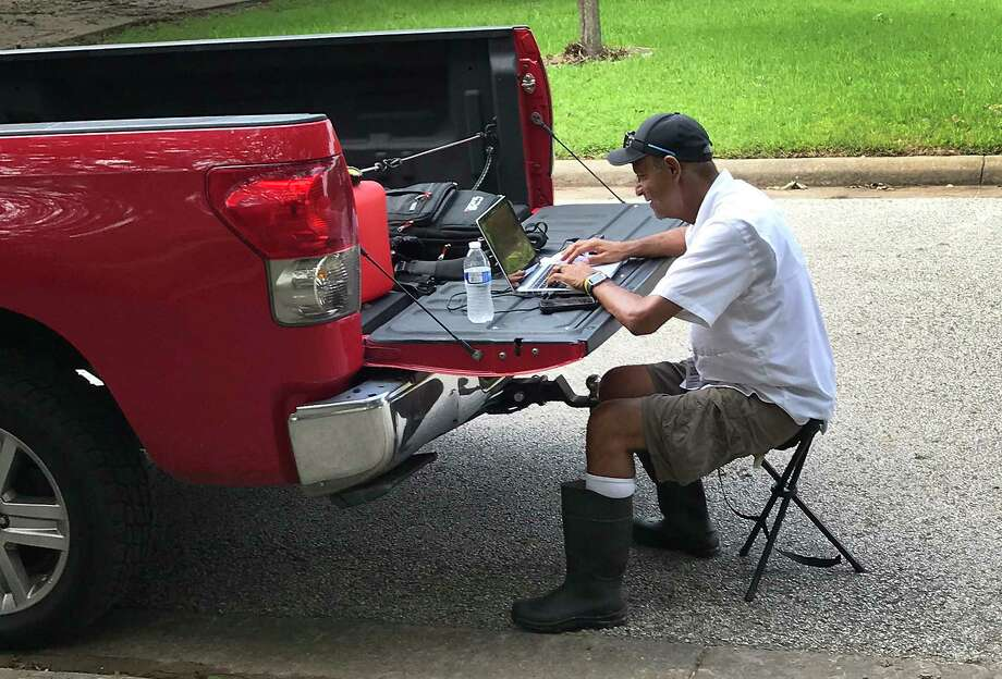 Houston Chronicle Staff Photographer Steve Gonzales works from the back of his pick-up while covering the aftermath of Hurricane Harvey Wednesday, Aug. 30, 2017, in West Columbia.  ( St. John Barned-Smith / Houston Chronicle ) Photo: St. John Barned-Smith, Houston Chronicle / Handout