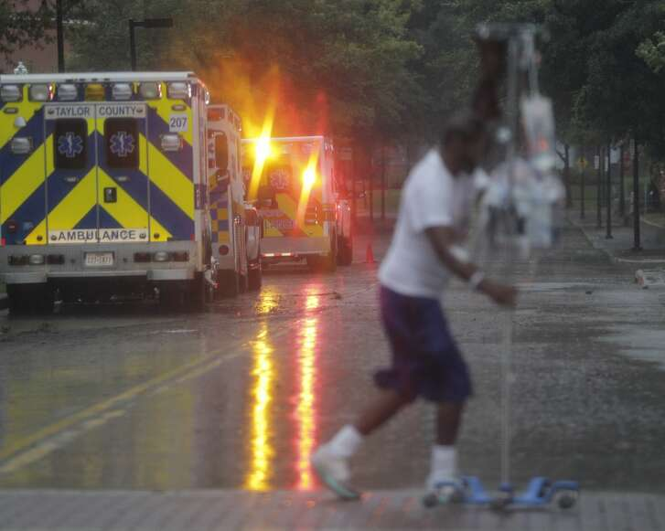 A patent returns from a smoke break as ambulances line up to evacuate some of the ICU patients out of Ben Taub Hospital in Houston as Tropical Storm Harvey inches its way through the area on  Monday, Aug. 28, 2017. ( Elizabeth Conley / Houston Chronicle )