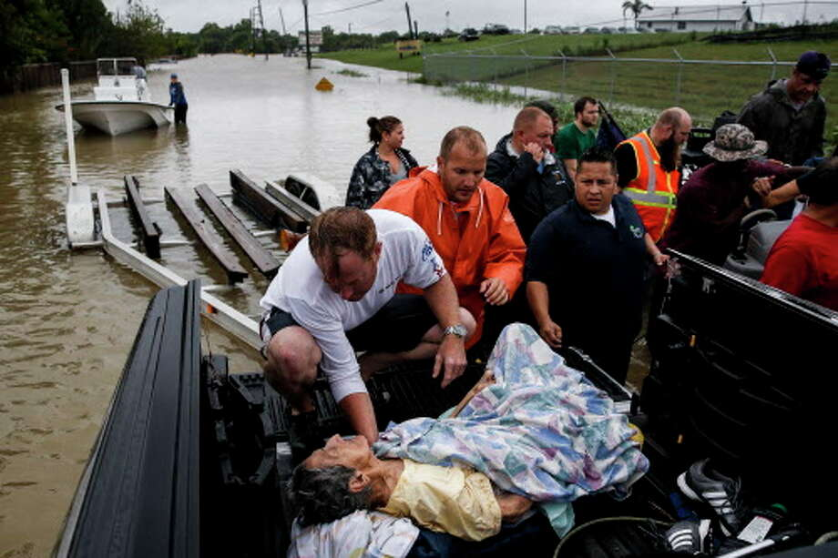 A rescuer moves Paulina Tamirano, 92, from a boat to a truck bed as people evacuate from the Savannah Estates neighborhood as Addicks Reservoir nears capacity Tuesday, Aug. 29, 2017 in Houston. ( Michael Ciaglo / Houston Chronicle) Photo: Michael Ciaglo/Houston Chronicle