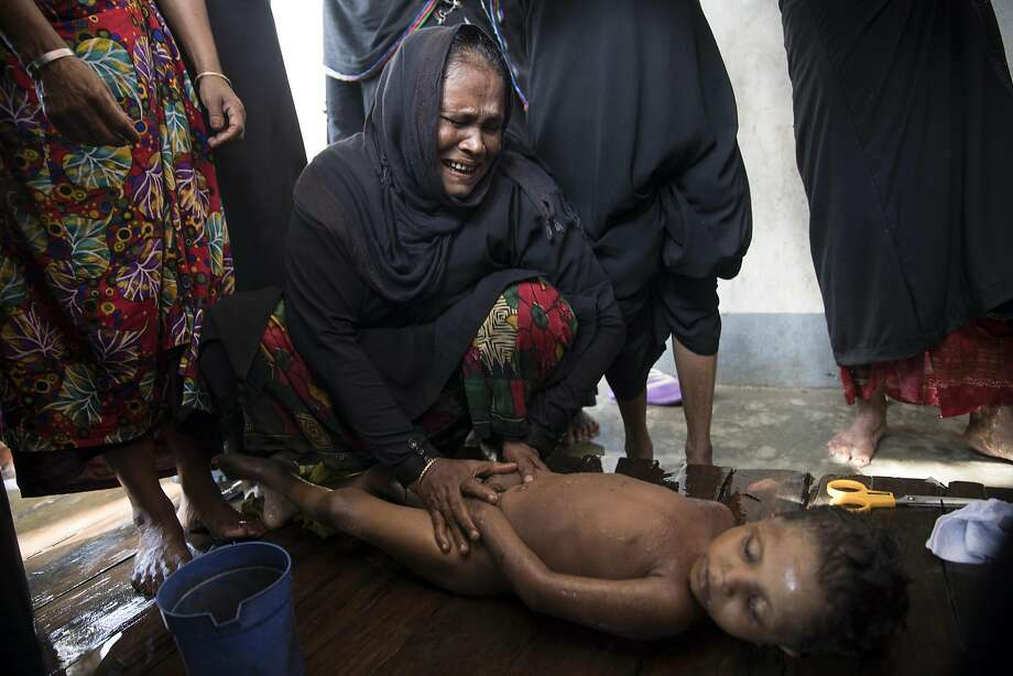 A woman weeps while preparing the body of a child for a funeral. More than 60 people died when a boat carrying Muslim refugees from Myanmar sank off the coast of Bangladesh. Photo: Paula Bronstein, Getty Images