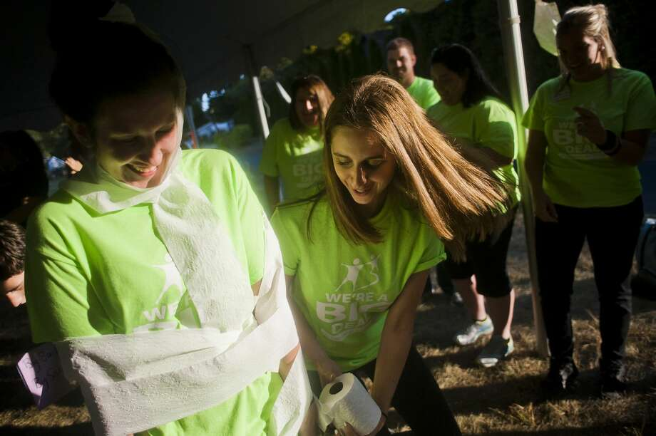 Rachel Sulkowski with Big Brothers Big Sisters, right, wraps Allie Schroeder in toilet paper as they compete in the United Way of Midland County Agency Games fundraising event on Thursday, Sept. 28, 2017 at the Greater Midland Community Center. Five of the 25 agencies that receive funding from the United Way of Midland County competed and raised money on during the event with a variety of yard games. (Katy Kildee/kkildee@mdn.net) Photo: (Katy Kildee/kkildee@mdn.net)