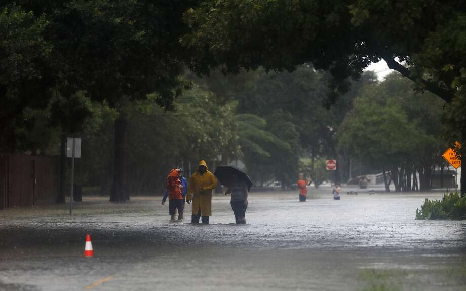 People walk through high water on Taylor Street in the Heights, after heavy rain from Hurricane Harvey fell overnight,  Sunday, Aug. 27, 2017, in Houston.  ( Karen Warren / Houston Chronicle ) Photo: Karen Warren, Houston Chronicle