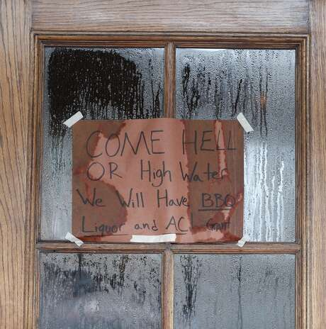 "The sign on the door of Pinkerton's BBQ on Airline in the Heights reads ""Come Hell or High Water, we will have BBQ, liquor and AC!"" inside they were serving people after heavy rain from Hurricane Harvey fell overnight,  Sunday, Aug. 27, 2017, in Houston.  ( Karen Warren / Houston Chronicle ) Photo: Karen Warren, Houston Chronicle"