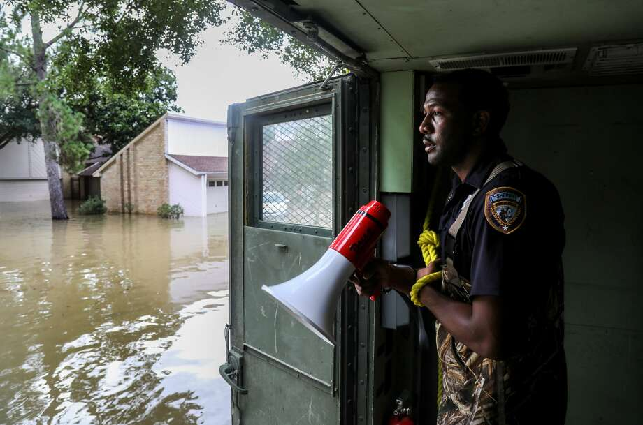Harris County Sheriff's Deputy Rick Johnson pauses to listen for people's voices as they search for people in a neighborhood inundated by water from the Addicks Reservoir, Wednesday, Aug. 30, 2017, in Houston. ( Jon Shapley  / Houston Chronicle ) Photo: Jon Shapley/Houston Chronicle
