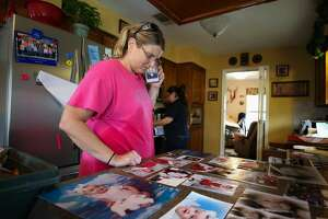 Laura Gill speaks on her phone while looking at family photos that are drying from their flooded home on Bayou Woods Drive after Tropical Storm Harvey Wednesday, Aug. 30, 2017, in Baytown, Texas. ( Godofredo A. Vasquez / Houston Chronicle )