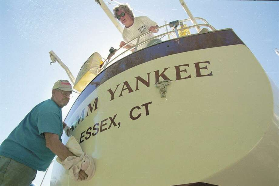 Kay Jacobs of Waterbury keeps an eye on husband Bob as he waxes the topsides of their boat, Damm Yankee, at Portland's Yankee Boat Yard. Photo: Middletown Press File Photo
