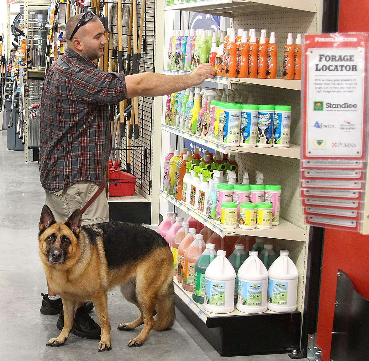 Derrek Guertin looks at pet shampoo as Kona stands by his side in the new Tractor Supply Co. store in Newtown, Conn., on Friday, Sept. 30, 2017.