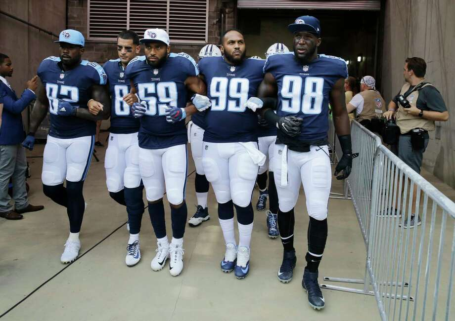 FILE - In this Sept. 24, 2017, file photo, Tennessee Titans' Delanie Walker (82), Marcus Mariota (8), Wesley Woodyard (59), Jurrell Casey (99) and Brian Orakpo (98) walk to the field with arms linked after the national anthem had been played before an NFL football game against the Seattle Seahawks in Nashville, Tenn. Walker says he and his family have received death threats since he told fans not to come to games if they felt disrespected by NFL players' protests. Walker shared the threats Thursday night, Sept. 28, 2017, in a social media post. (AP Photo/James Kenney, File) Photo: James Kenney, FRE / FR171271 AP