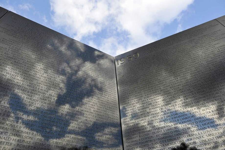 Clouds are reflected on the Vietnam War Memorial during ceremonies for Veterans Day on November 11, 2011, in Washington, DC. Photo: MLADEN ANTONOV, Staff / ONLINE_YES