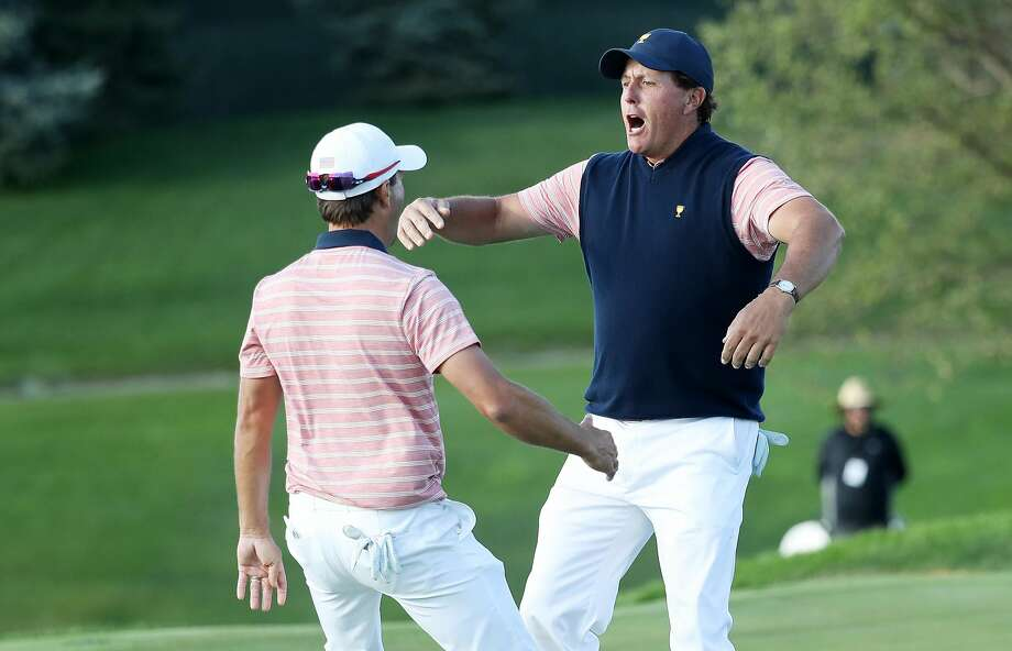 "Phil Mickelson (right) and partner Kevin Kisner attempt the ""Three Amigos"" dance after their win. Photo: Rob Carr, Getty Images"