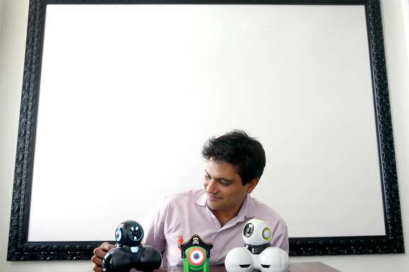 Vikas Gupta, founder and CEO of Wonder Workshop, interacts with a pair of his company's Cue robots along with a bot (center) from the Dot Creativity Kit in San Francisco, Calif. on Friday, Sept. 29, 2017.