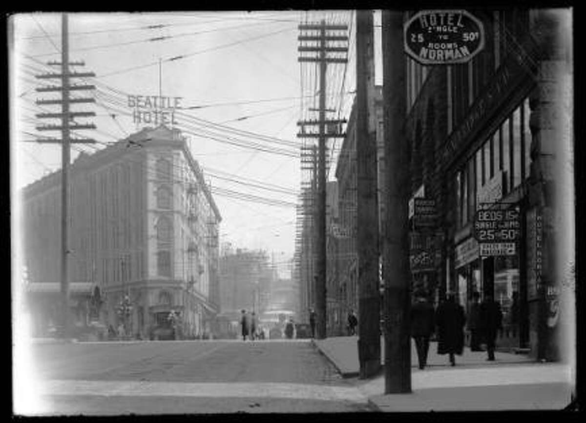 Looking east from First Avenue and Yesler Way, circa 1910. Pioneer Place and Hotel Seattle are on the left. The City Light substation is visible farther up the hill at Yelser and Seventh. The Hotel Norman, Riverside Quarry Inc., a dentistry, and the Olympic Block appear on the right. -SPL