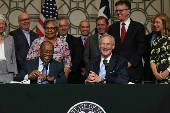 Gov. Greg Abbott, right, and Mayor Sylvester Turner praise each other for working together as a team during a joint press conference at Houston City Hall Frida  Abbott presented a $50 million dollar check from the state to assist Houston with Hurricane Harvey relief. ( Yi-Chin Lee / Houston Chronicle )