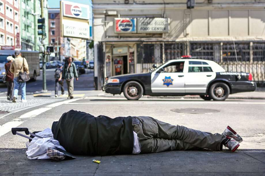 A homeless man sleeps on the sidewalk on Ellis Street and Jones, an area known for it's chronic homeless encampments, while a police car passes by on Thursday, June 15, 2017 in San Francisco, Calif. Photo: Amy Osborne, Special To The Chronicle