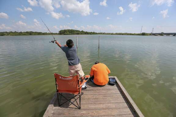Sampson Mann, 7, casts a line with his neighbor Eddie Yazie at W.C. Britton Park in Baytown. The water is showing higher than normal contamination.