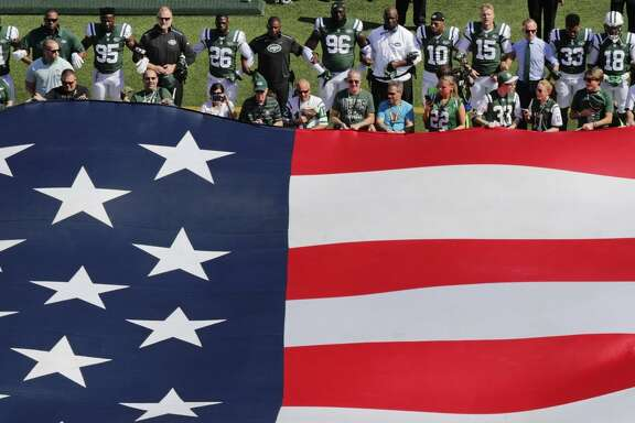 The New York Jets lock arms for the national anthem before a game last Sunday against Miami.
