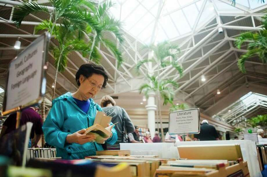 Ilhae Lee of Midland peruses books in the Literature section during the annual AAUW book sale Friday, Sept. 29, 2017 at Midland Mall. The sale began on Friday morning and continues through Sunday, Oct. 1. (Katy Kildee/kkildee@mdn.net)