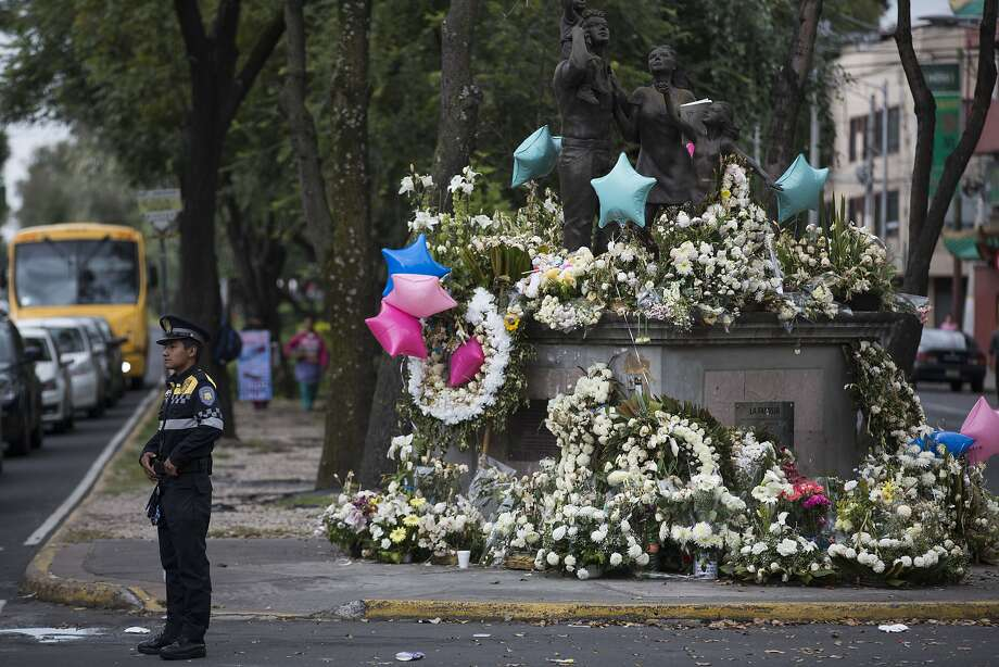 An officer directs traffic near a memorial to 26 people who died when part of a school collapsed in the Mexico City earthquake. Photo: Moises Castillo, Associated Press