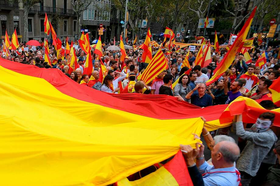 People hold a giant Spanish flag during a demonstration against independence in Catalonia, on September 30, 2017 in Barcelona. Hundreds of people, many waving red and yellow Spanish flags, rallied in Barcelona in favour of Spanish unity today, a day before a banned independence referendum in Catalonia. / AFP PHOTO / LLUIS GENELLUIS GENE/AFP/Getty Images Photo: LLUIS GENE, AFP/Getty Images
