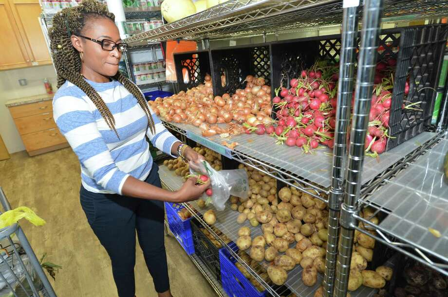 Chiky Beary, a single mother, picks up some fresh produce such as potatoes, corn, peppers carrots and onions while filling her shopping cart at the Person-to-Person food pantry on Wednesday in Norwalk. Healthy food options along with the regular staples for those in need are available for clients. Photo: Alex Von Kleydorff / Hearst Connecticut Media / Norwalk Hour