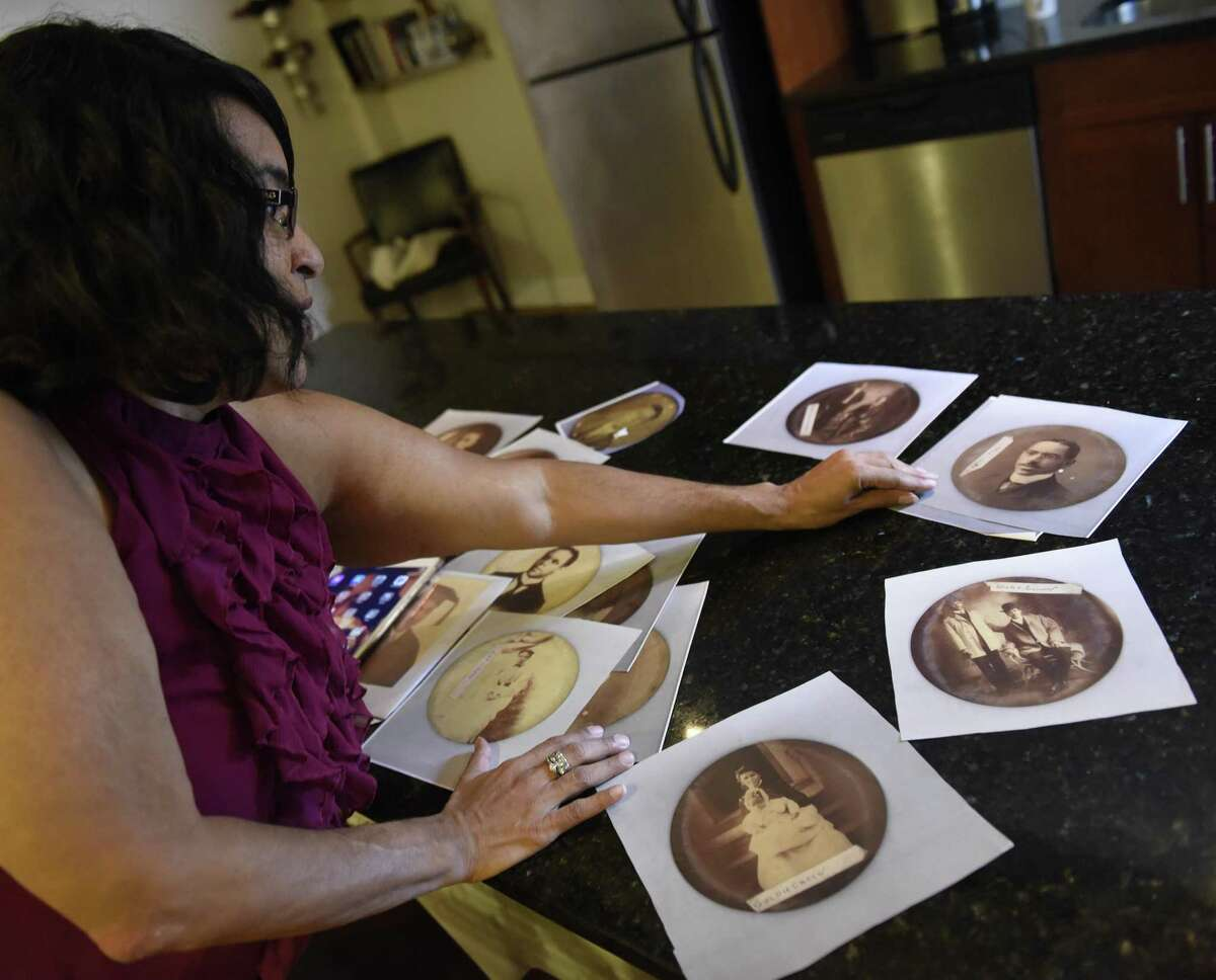 Teresa Vega shows tintype photographs of her distant ancestors at an apartment in the Inwood neighborhood of New York, N.Y. Tuesday, Sept. 26, 2017. Vega researched her family members, descended from slaves, who farmed in an area around Round Hill Road in Greenwich referred to as Hangroot.
