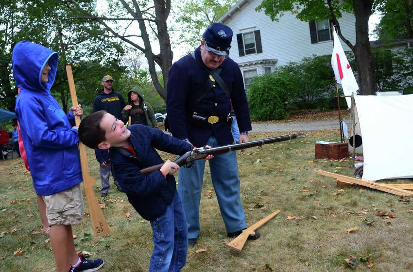 Brennan Kane, 6, of New Britain, uses all his strength to hold up a replica of a Civil War era rifle as reenactor John Morrison gives kids a training session using wood toy rifles during a Civil War encampment of Company F of the 14th Connecticut Infantry Regiment at the Stratford Historic Society in Stratford, Conn., on Saturday Sept. 30, 2017. Members of the original company served in several major battles during the Civil War including the Battle of Antietam in MD and the Battle of Gettysburg in PA.