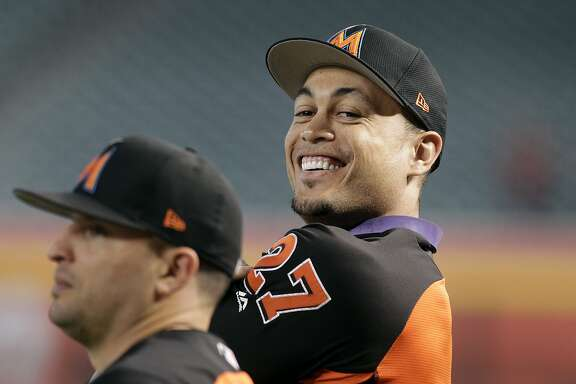 Miami Marlins' Giancarlo Stanton (27) smiles as he waits to take batting practice before a baseball game against the Arizona Diamondbacks, Friday, Sept. 22, 2017, in Phoenix. (AP Photo/Ralph Freso)