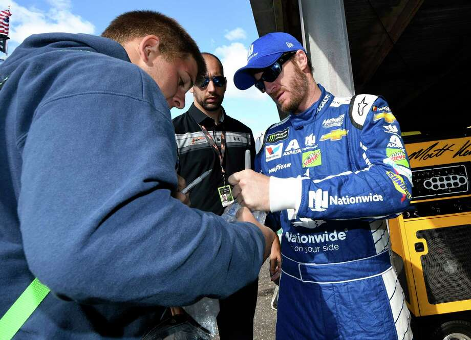 Dale Earnhardt Jr., right, signs for a fan before practice for the NASCAR Cup series auto race, Saturday, Sept. 30, 2017, at Dover International Speedway in Dover, Del. (AP Photo/Nick Wass) Photo: Nick Wass, FRE / FR67404 AP